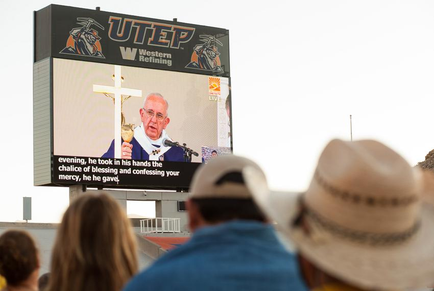 A group watches Pope Francis giving Mass on TV during the Two Nations One Faith event held at Sun Bowl Stadium on Wednesday,…