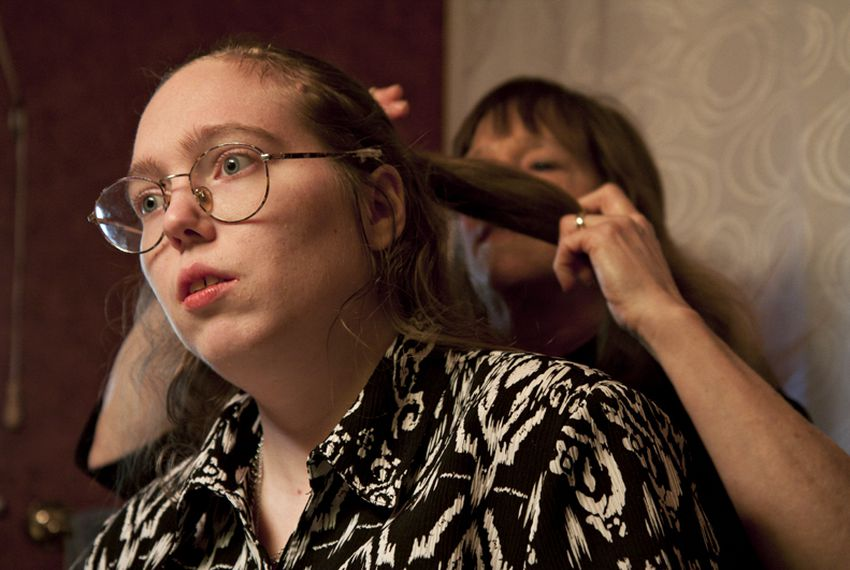 Barbara Cullison does her daughter Audrey's hair. Audrey, who is autistic, risks losing her Medicaid waiver services because of state budget cuts.