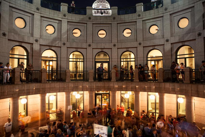 Demonstrators in favor of HB2 rally inside the State Capitol Open Air Rotunda wreathed by marching opposition demonstrators …