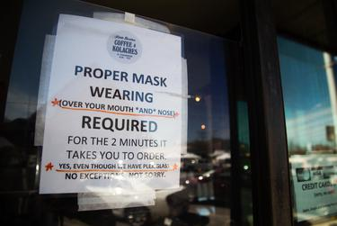 A sign outside of Little Brother Coffee & Kolaches asks customers to wear a mask inside the South Austin business on March 3, 2021.