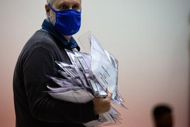 A Harris County election worker carries a stack of envelopes containing ballot information at NRG Arena on Nov. 3, 2020, in Houston.