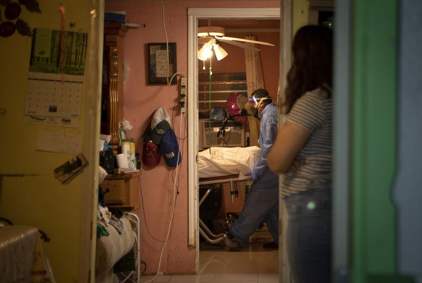 Juan Lopez works to remove a dead body from a home in McAllen. The person recently died from COVID-19. July 17, 2020.