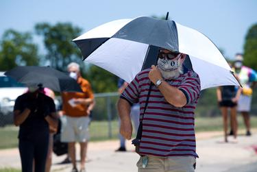 A voter uses an umbrella for protection from the sun. Voters waited in 100 degree temperatures outside the Pflugerville ISD Rock Gym  on Tuesday.