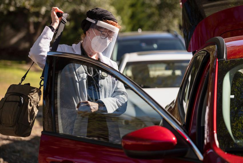 Medical doctor Sandra Petersen wearing a face shield and mask grabs her work bag with her medical tools before seeing COVID-…
