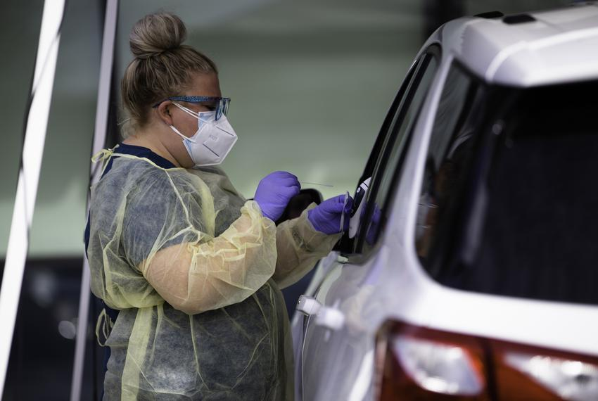 A nurse conducts a swab test for COVID-19 on a patient in a drive-thru station at the Austin Emergency Center at Mueller on …