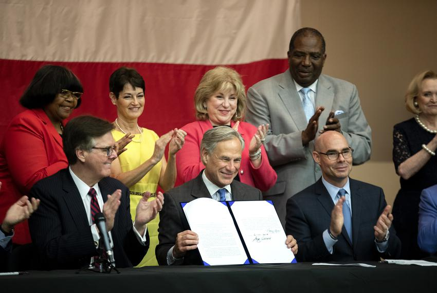 Gov. Greg Abbott signs the $11.6 billion school finance bill into law while surrounded by lawmakers at Parmer Lane Element...