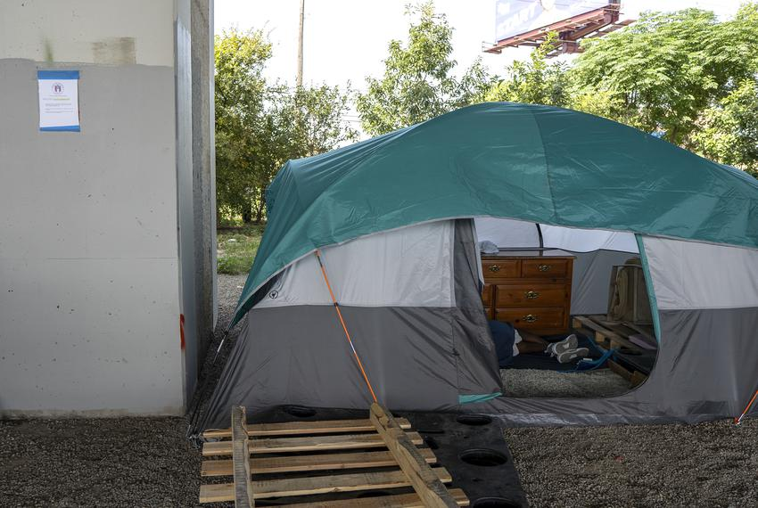 """A """"Notice of Cleanup and Property Removal"""" sign hangs on a pillar next to a tent underneath Ben White Blvd. in Austin on Jul…"""