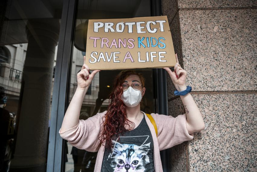 """Ada-Rhodes Short holds up a sign that reads """"Protect Trans Kids Save a Life"""" at an event held by Equality Texas at the Capit…"""