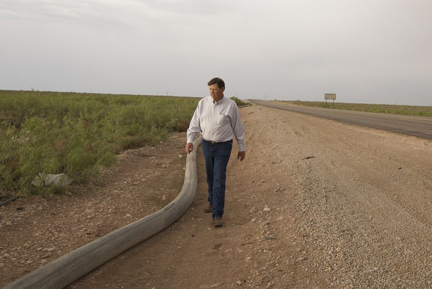 New Mexico State Land Commissioner Aubrey Dunn walks along Ranch Rd 652 at the Texas-New Mexico border on May 23, 2018, next to a water line that runs from Loving County, Texas, to Lea County, New Mexico.