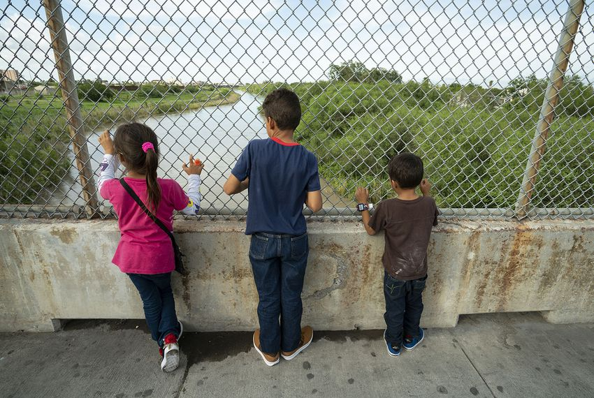 Javier Alejandro Vindel-Rodriguez (center) looks down at the Rio Grande with his siblings, Yenci (left) and Jesus Samuel on Sunday, June 24, 2018. Their family left Honduras in January, and have slowly made their way to Matamoros.