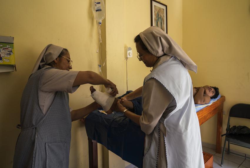 Nun Juana Aguilar, 56, left, and nun Pilar Méndez, 54, right, provide wound care to Guatemalan migrant Miguel Angel López, 1…