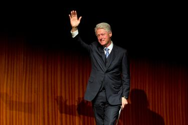 Former President Bill Clinton waves as he walks off stage following a speech during the Civil Rights Summit on April 9, 2014.  