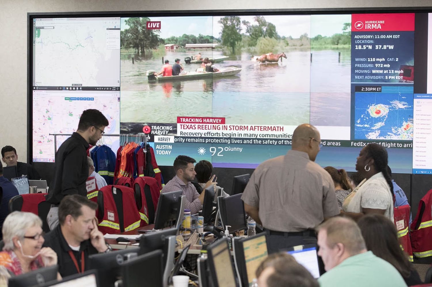 With video of southeast Texas flooding rolling in the background, state emergency workers tackle Hurricane Harvey-related crises at the Texas DPS Emergency Operations Center (EOC) on Sept. 1, 2017.