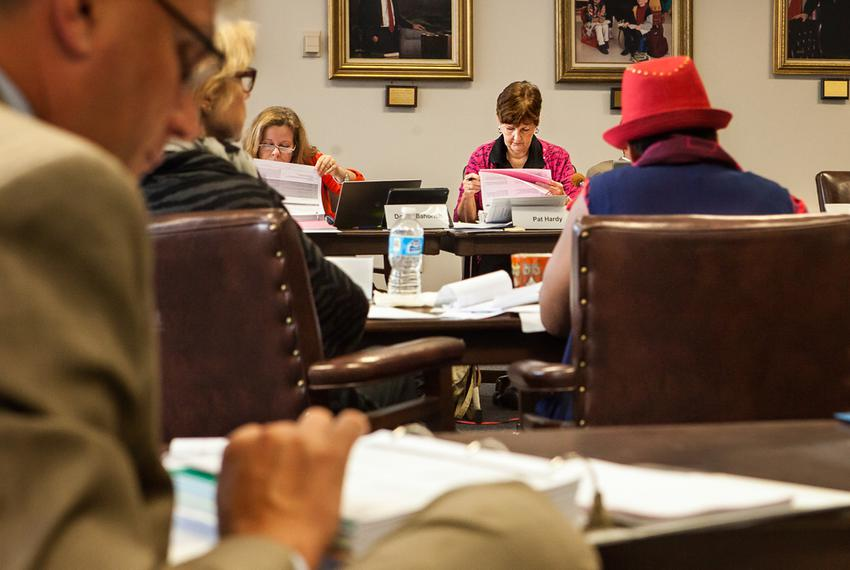 State Board of Education members work their way through proposed revisions to social studies textbooks at a meeting with p...