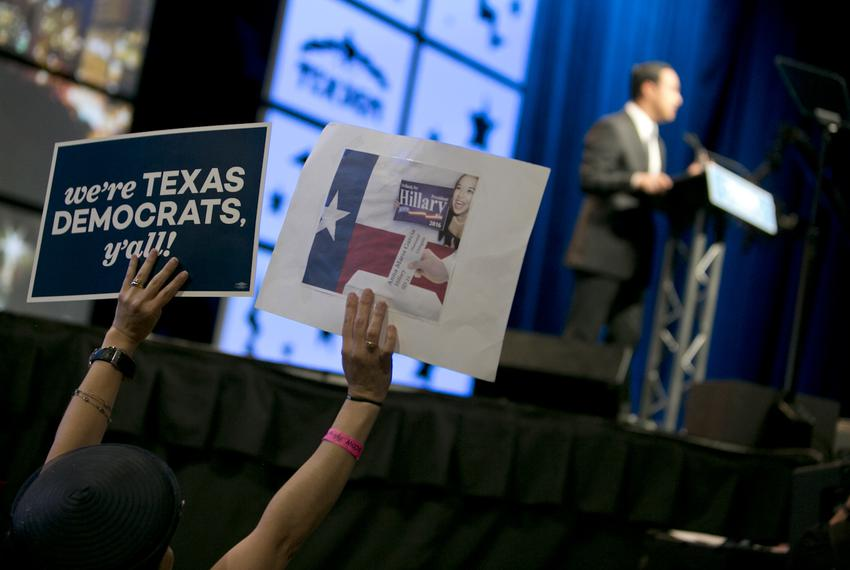 A Democratic convention attendee holds up signs during remarks by U.S. Congressman and convention chair Joaquin Castro, D-Sa…