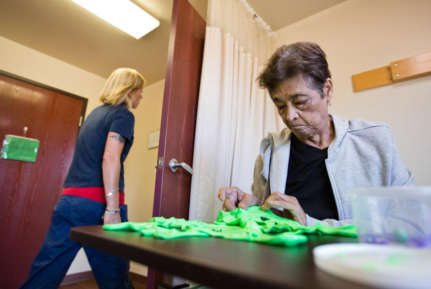 A patient at Sagebrook Health Center, a nursing facility in Cedar Park, kneads putty to build fine-motor coordination and ...