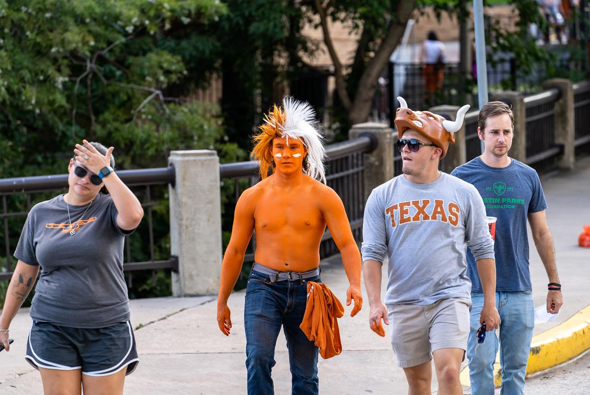 A UT fan with his body painted burnt orange walks towards the stadium for the first home football game of the season at the University of Texas at Austin on Sept. 12, 2020.
