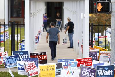 Campaign workers make pitches to voters outside the Metropolitan Multi-Service Center in Houston on Nov. 5, 2019.
