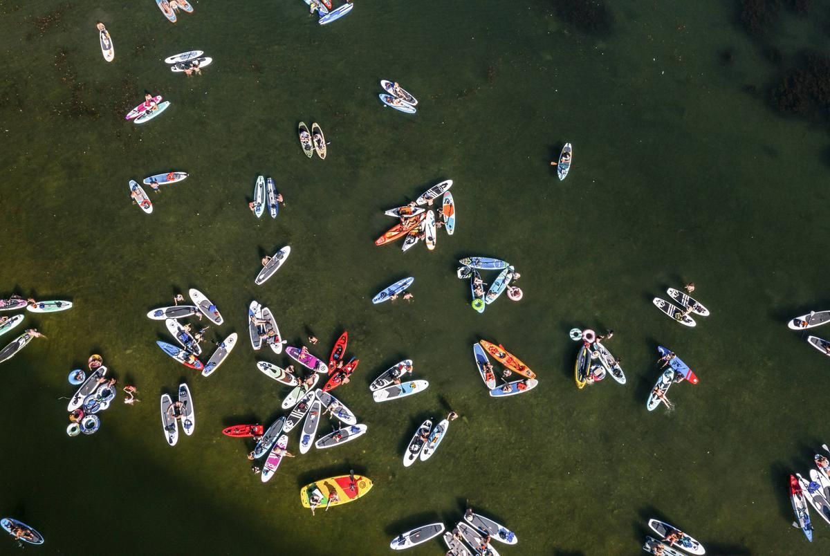 Kayak's, Paddle Boards, and other water craft gather at a shallow spot on Lady Bird Lake in downtown Austin on Friday, June 14, 2021.