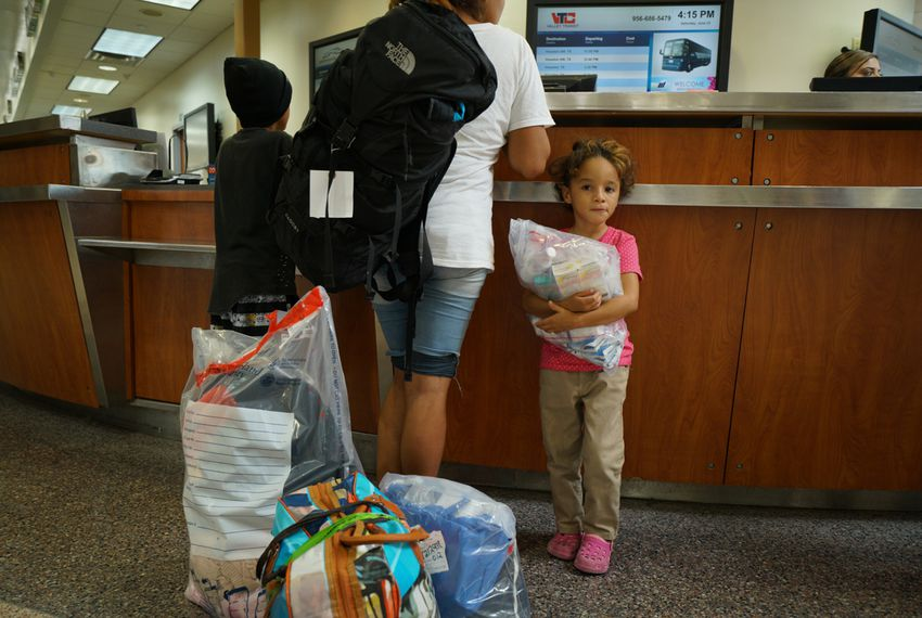 A young girl named Genesis waits with her brother Jose as their mother gets bus tickets in McAllen on June 23, 2018. Her family was camped out on the Brownsville/Gateway International Bridge for four days, seeking asylum.
