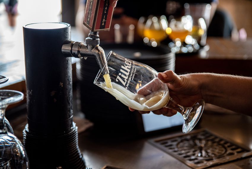 Red Godwin pours a beer behind the bar at Zilker Brewery in Austin. Texas Gov. Greg Abbott signed new laws that will allow breweries to sell beer to go out of their taprooms, and allow food and wine retailers to deliver beer or wine directly to customers. The new laws go into effect Sept. 1.