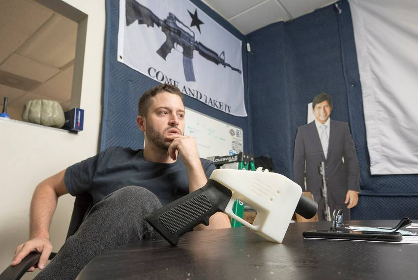 Cody Wilson sitting with a 3D-printed plastic gun made several years ago. Behind him is a cutout of California state Rep. Kevin de León, whom Wilson calls his group's patron saint.