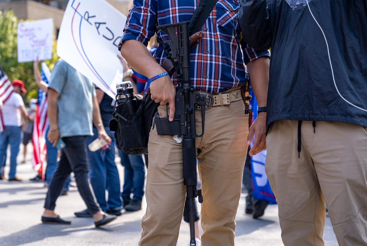 A man carrying an assault rifle participated in the