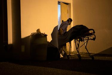 Juan Lopez removes a dead body from the back of his vehicle at a funeral home parking lot in McAllen. Lopez picked up the body at a local home and is delivering it to the funeral home. July 17, 2020.
