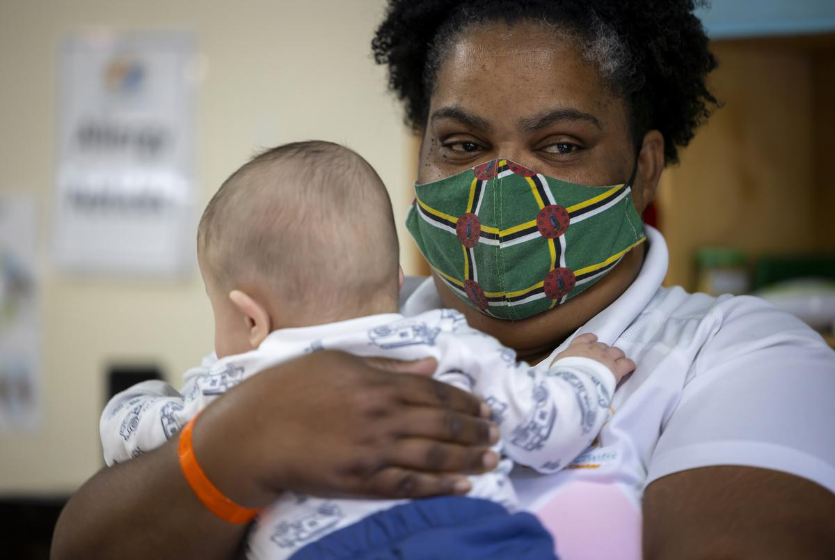 Museum District Childcare Center's Louvaine Reid comforts a baby on their first day at the center on Sept. 1, 2021. The center still has several COVID-19 protocols in place, such as keeping parents outside and requiring staff to wear masks.