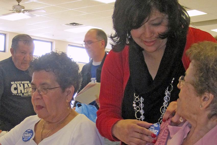 Norma Chavez works attaches a campaign button to the sweater of one of her supporters at an El Paso senior center before the…