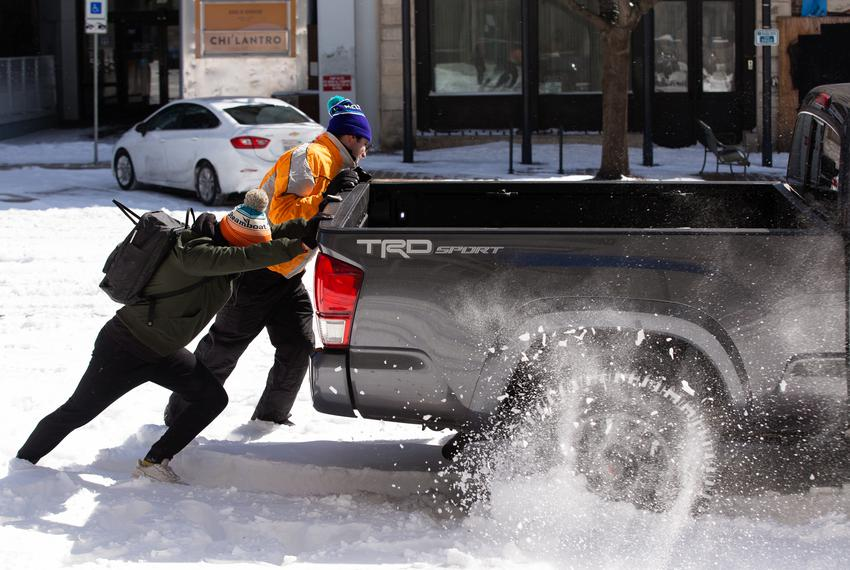 People push on the back of a truck to attempt to get the vehicle unstuck from the snow in Austin on Feb. 15, 2021.