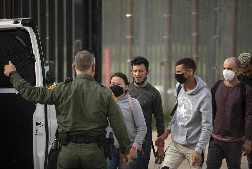 A group of migrants walks onto a Customs and Border Protection vehicle after being apprehended near the U.S. and Mexico bord…