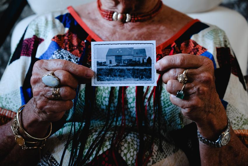 Mina Verton holds up a photo of her family's farm house, which was swept away in the 1953 North Sea flood.