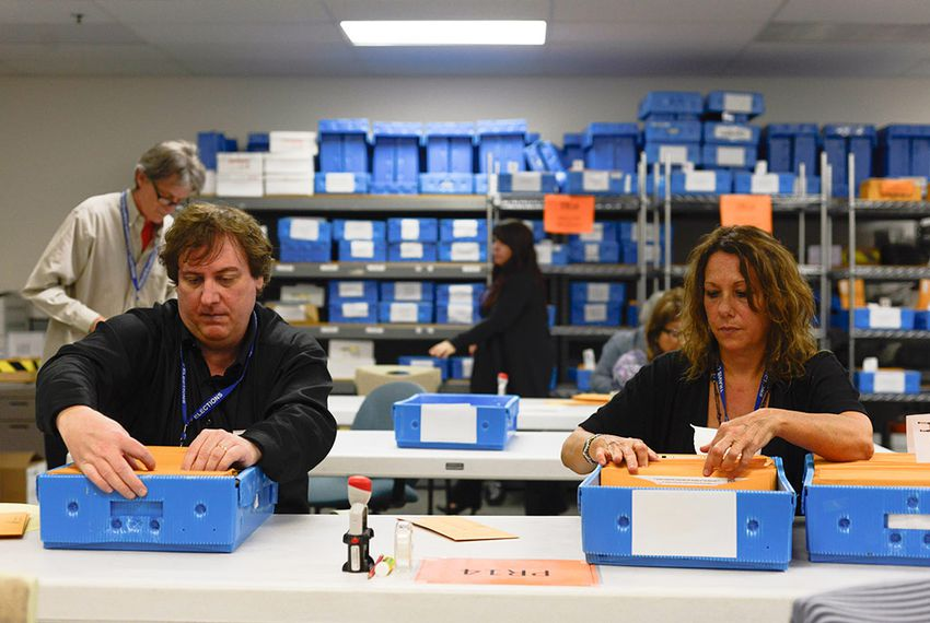 From left, Ballot by mail clerks John Paris and Carol Mizelle organize ballot packages at the Travis County Elecions division in Austin, Texas. May 19, 2014.