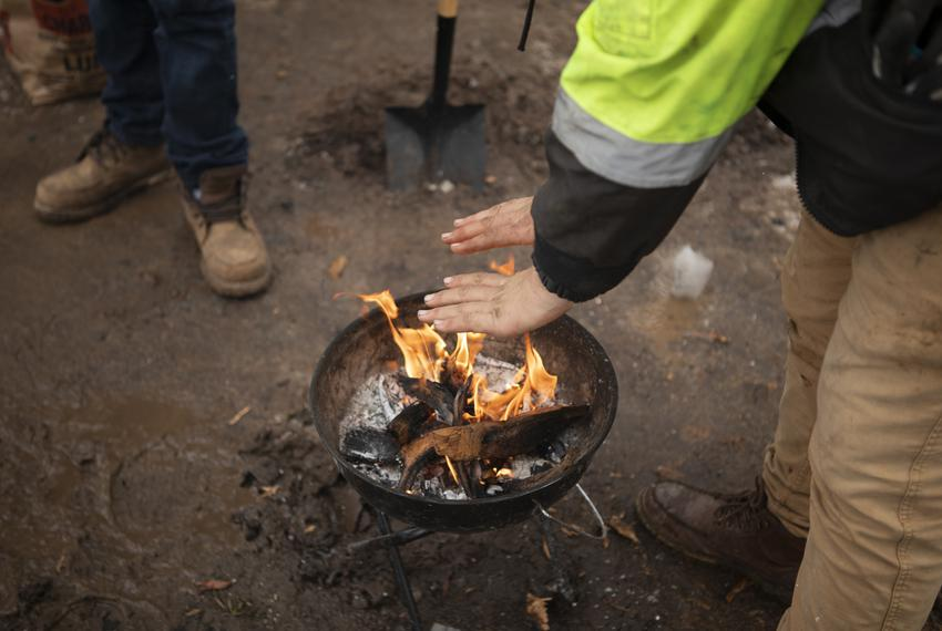 Jacob Duran warms his hands over a grill after his apartment lost power due to the severe winter storm that hit the state. F…