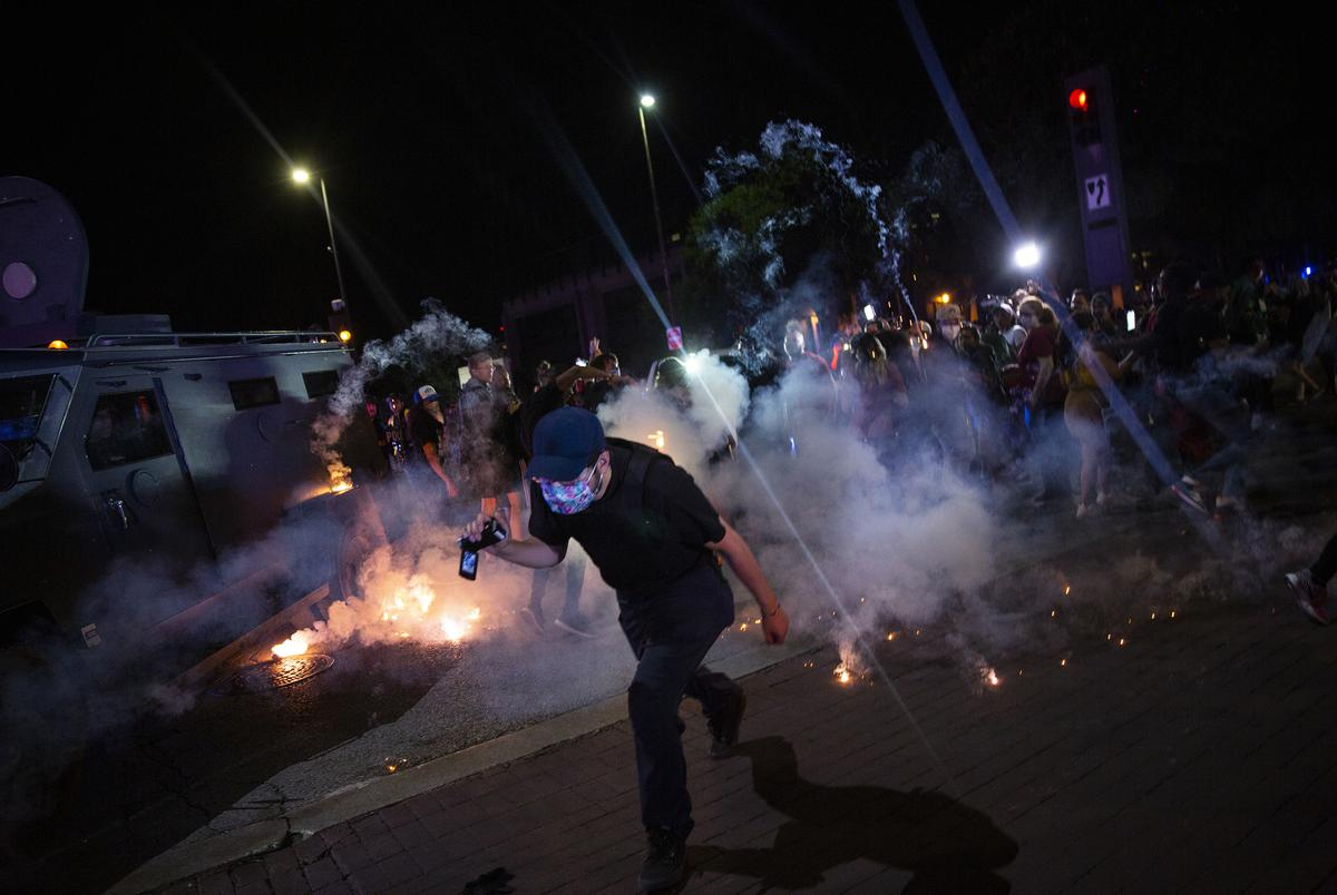 Protesters run away as Dallas police officers launch tear gas after a confrontation during a rally for George Floyd on May 29, 2020.