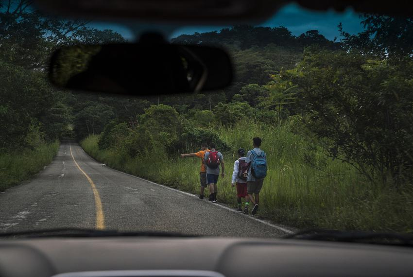"""Migrants walk through Highway México 307 on Oct. 21 near Palenque, Chiapas. The highway is also known by the locals as """"El G…"""