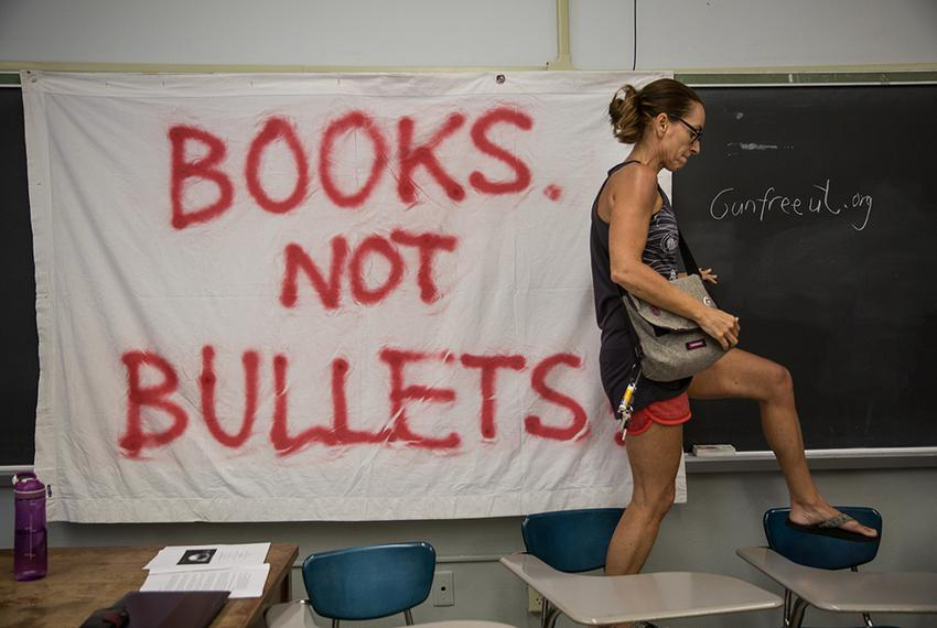 "Pascale Bos, an associate professor at UT Austin, walks over desks after pinning up a ""Books not bullets"" sign at a peace an…"