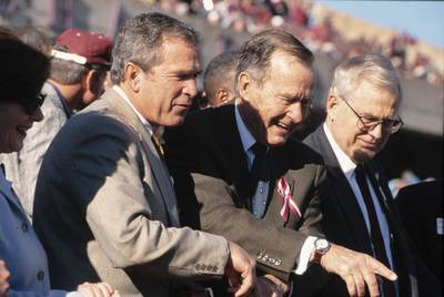 George H.W. Bush and son George W. Bush attend a Texas A&M-Texas football game in 1999 at Kyle Field. |