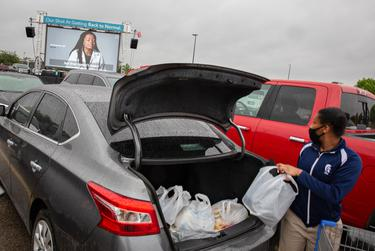 Shoppers load their cars with groceries as a Texas Department of State Health Services advertisement encouraging people to get the COVID-19 vaccine plays in a Walmart parking lot in Fort Worth on April 30, 2021.