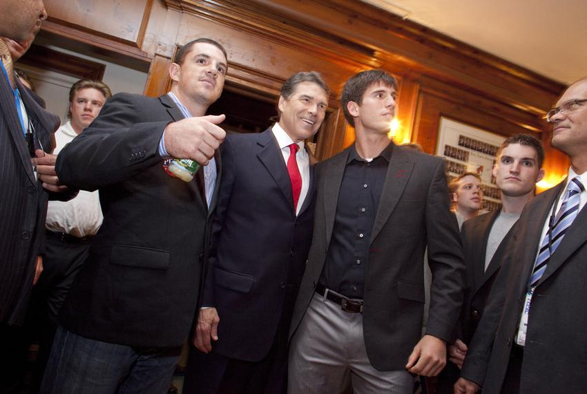 Gov. Rick Perry greets students during a visit to a Dartmouth fraternity house after the Republican presidential debate on O…