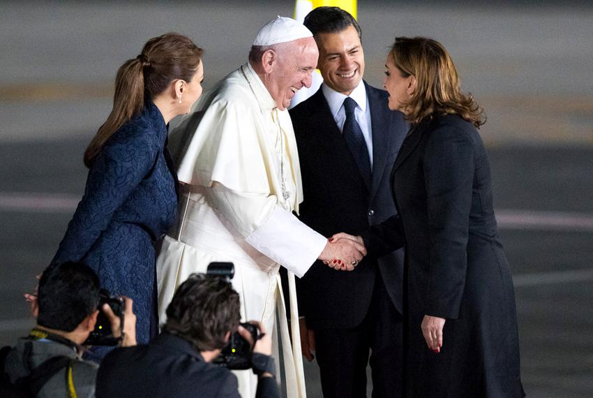 Pope Francis greets a woman as he is escorted by Mexican President Enrique Peña Nieto and his wife, Angelica Rivera de Peña.…