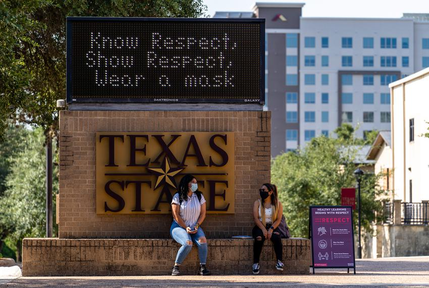 Two students sit under a sign encouraging students to wear a mask on the first day of classes for the fall semester at Texas…