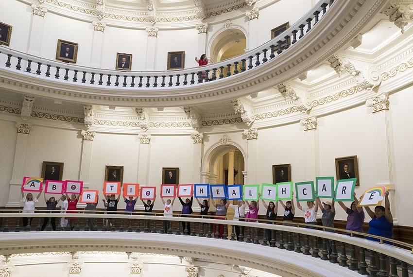 "Women holding signs spelling out ""abortion = healthcare"" line the second floor Capitol rotunda on July 27, 2017, after the H…"