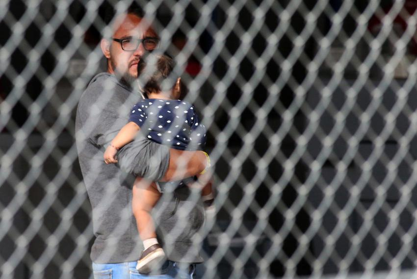 A migrant holds an infant child inside a holding area under the Paso Del Norte International Bridge to be taken to area proc…