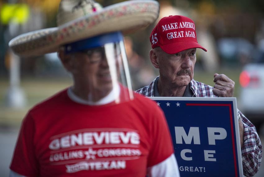 Jack Kennedy, right, sports a Make America Great Again cap while holding a Trump-Pence sign outside of the polling location …