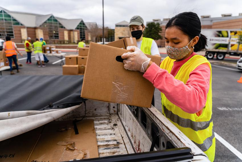 Tam Vo, right, a senior Biochemistry major at the University of Texas in Austin, loads a box of food into a truck. Vo is fro…