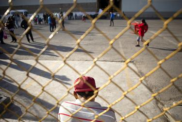 A young boy sits by the fence of the migrant shelter in Piedras Negras, Coahuila. A week before, the shelter held an estimated 1700 migrants, only several hundred remain as of Feb. 18, 2019.. The shelter is slated to close later  in the week.