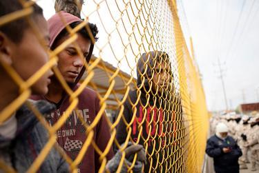 From left, Elmer de la Rosa, Orlando Jose Reyes and Carlos Lanza stand near the perimeter of the migrant shelter in Piedras Negras, Coahuila, on Feb. 9, 2019.