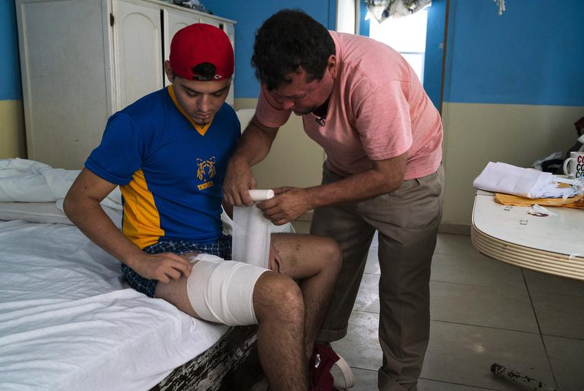 Nicaraguan migrant Bernardo Calero wraps a bandage around the leg of his son, Grisber, on Sept. 13, 2018, in Reynosa, Mexico…